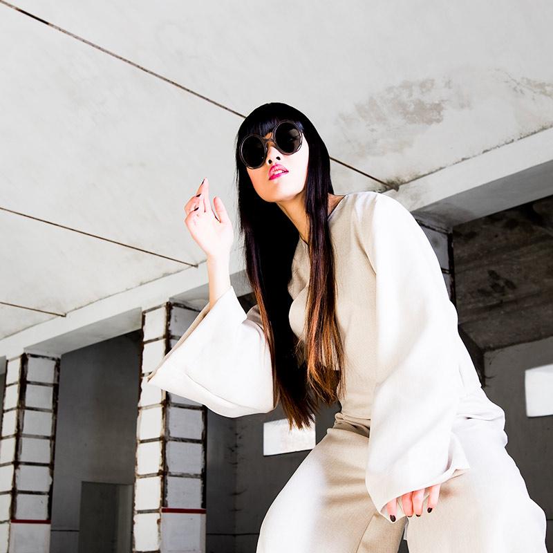 modella cinese con occhiali da sole indossa abito bianco tema styling